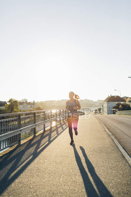 Young woman jogging on bridge in backlit — Stock Photo