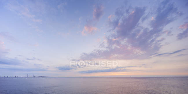 Scenic view of sunrise seascape under cloudy sky — Stock Photo