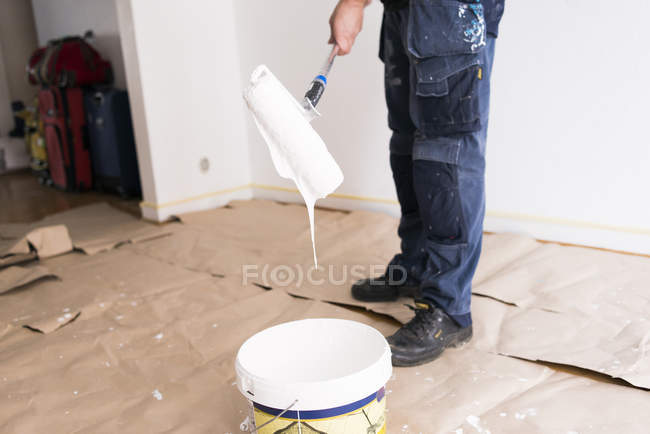 Man holding paint roller over bucket — Stock Photo