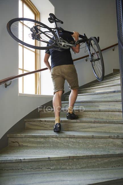 Низкий угол обзора велосипедиста, несущего велосипед по ступеням — стоковое фото