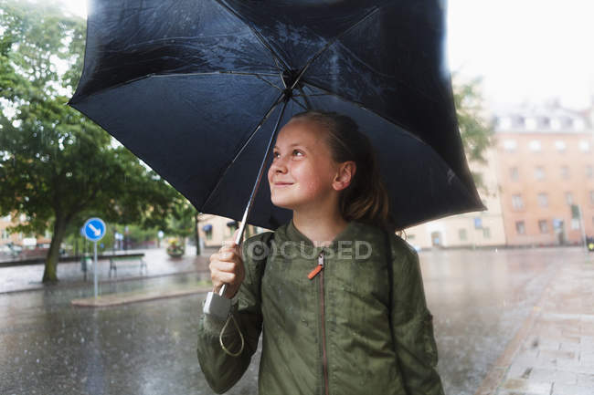 Girl carrying umbrella and smiling, focus on foreground — Stock Photo