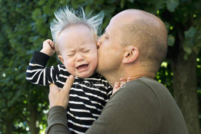 Отец целует плачущего маленького сына, избирательный фокус — стоковое фото