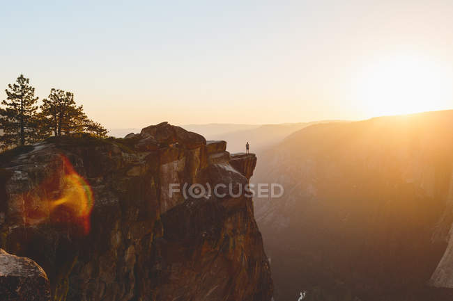 Scenic view of Yosemite National Park, man standing at edge of rock in background — Stock Photo