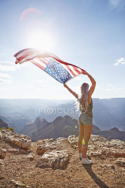 Молодая женщина, держащая нас флаг на Гранд-Каньон — стоковое фото