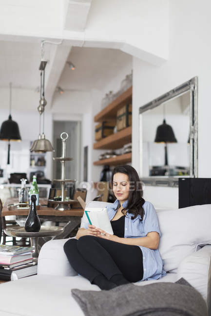 Woman reading book in living room — Stock Photo
