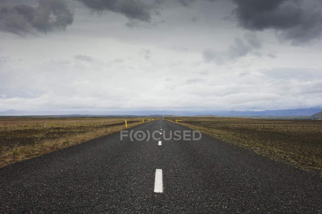 Road stretching through dry landscape under cloudy sky — Stock Photo