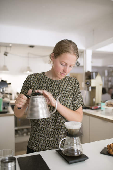 Woman pouring water into coffee drip — Stock Photo