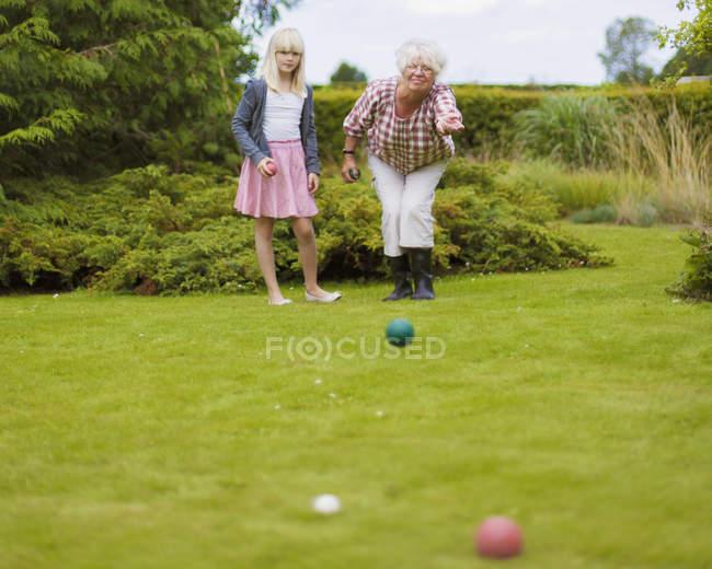 Menina que joga o petanca com a avó no jardim — Fotografia de Stock