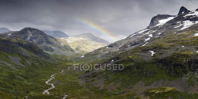 Gamma Jotunheimen e lussureggiante valle verde con arcobaleno in cielo — Foto stock