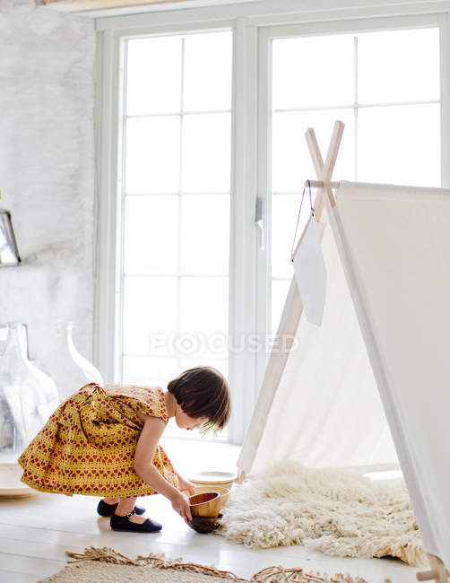 Chica creativa jugando al lado de la tienda en casa - foto de stock