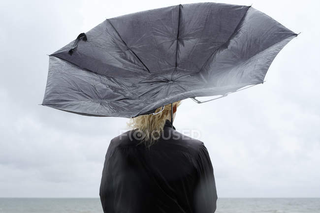 Woman under black umbrella watching Baltic Sea — Stock Photo