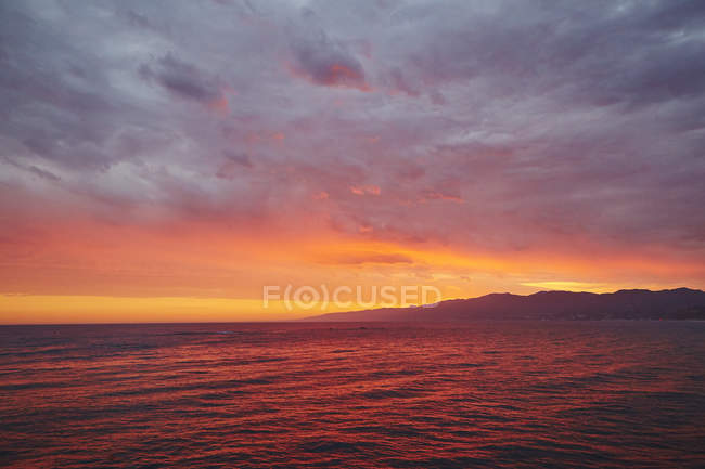 Seascape with silhouettes of mountains on sunset sky — Stock Photo
