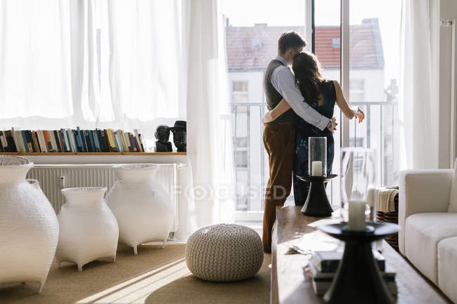 Rear view of couple hugging by window in living room — Stock Photo