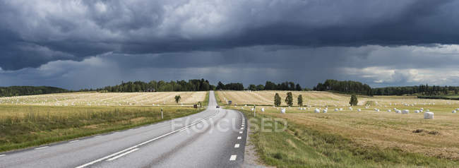 Storm clouds in sky over country road — Stock Photo