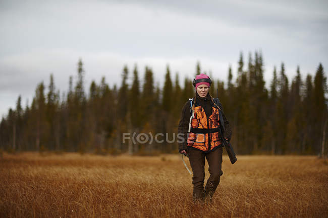 Female hunter walking in field, focus on foreground — Stock Photo