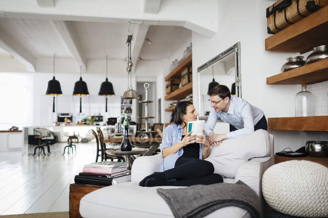 Mature couple talking in living room, focus on background — Stock Photo