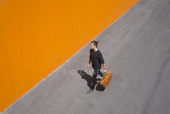 Vista elevada del hombre joven caminando con el equipaje de pared naranja - foto de stock