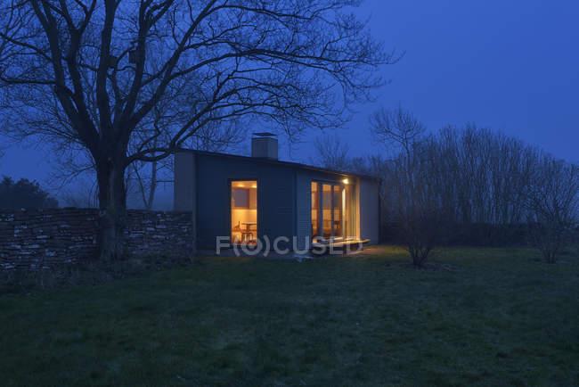 Освещенная небольшой современный дом ночью — стоковое фото