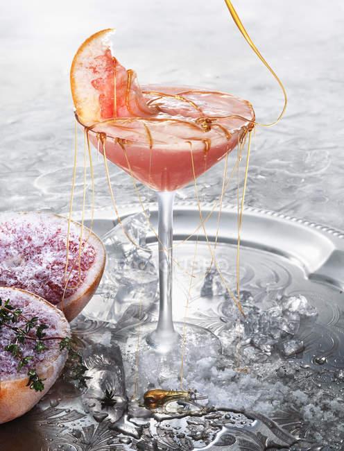 Коктейль с ломтик граната и розлива меда — стоковое фото