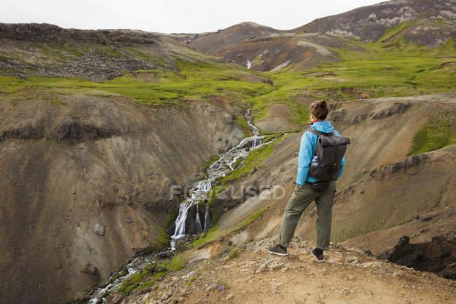 Turista che cerca al ruscello e cascate in valle rocciosa — Foto stock