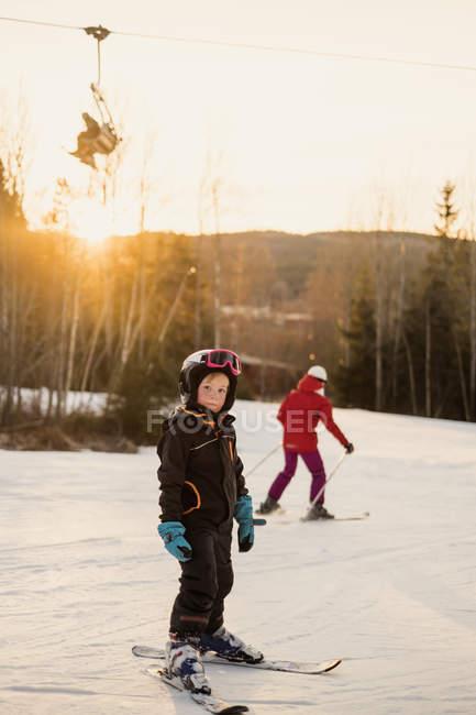 Menina, sorrindo e olhando para a câmera na pista de esqui — Fotografia de Stock