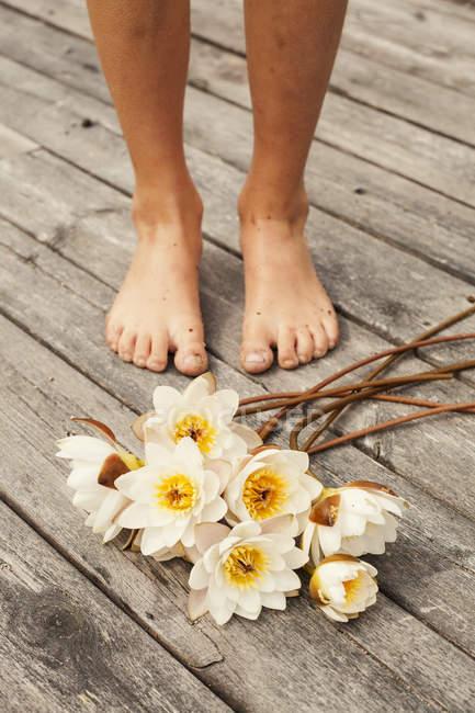 Blumen liegen neben Jungenfüßen — Stockfoto