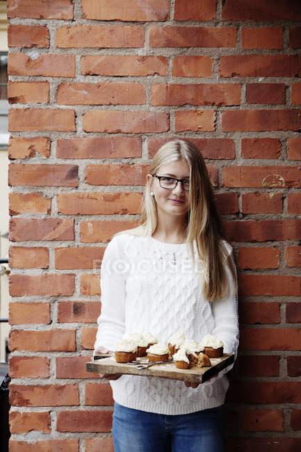 Menina com cupcakes contra parede de tijolo — Fotografia de Stock