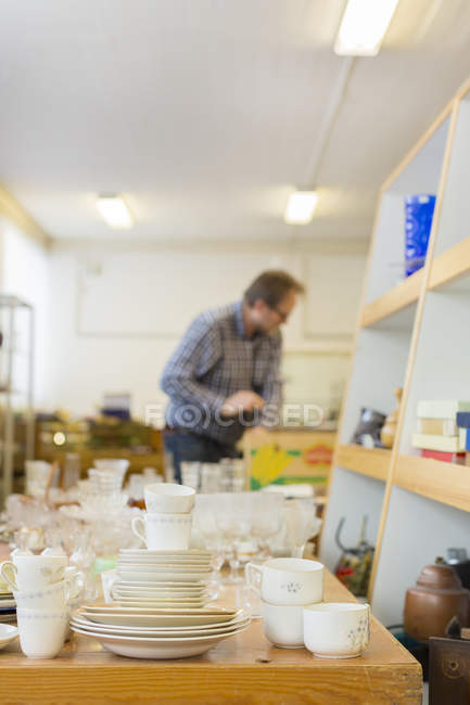 Man choosing plates in store, focus on foreground — Stock Photo