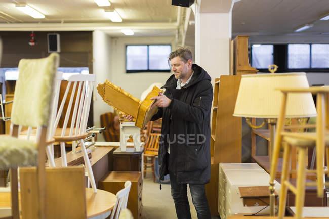 Homme choisissant des meubles en magasin, focus différentiel — Photo de stock