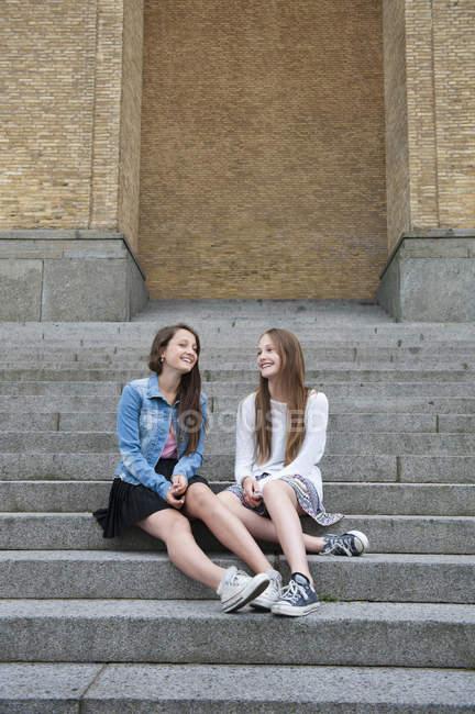 Дівчаток-підлітків, сидячи на сходах, зосередитися на передньому плані — стокове фото