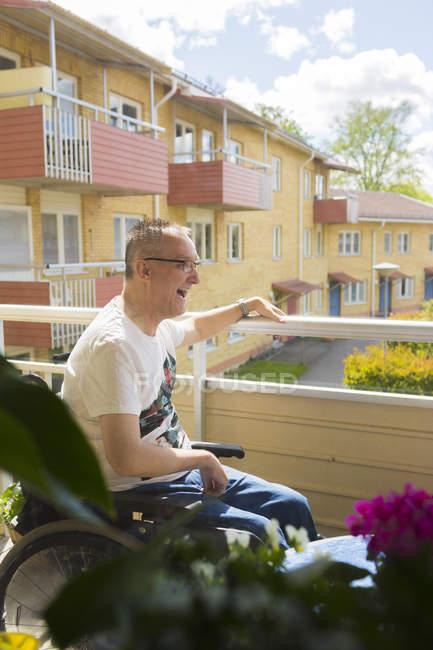 Mann im Rollstuhl auf Balkon, differenzierter Fokus — Stockfoto