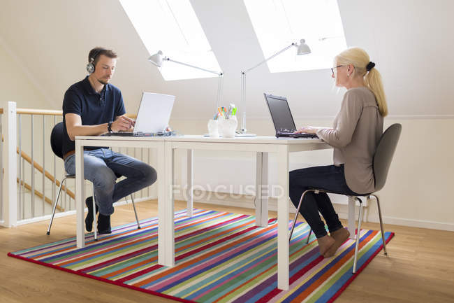 Vista laterale della coppia che lavora a casa — Foto stock