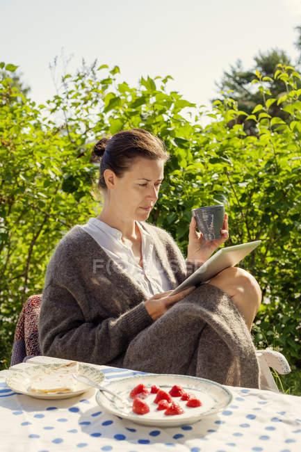 Женщина, использующая цифровой планшет летом — стоковое фото