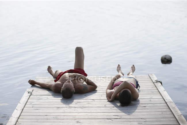 Homem e mulher deitada e banhos de sol no cais — Fotografia de Stock
