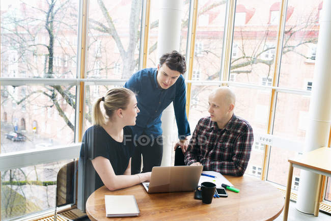 Office workers discussing work and using laptop — Stock Photo