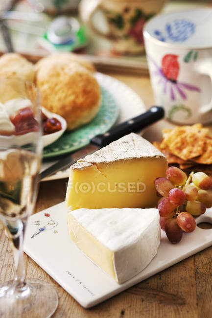Close-up of cheeses and fruits on table, focus on foreground — Stock Photo