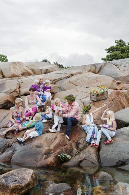 Grande famille pique-niquer sur les rochers au bord de la mer — Photo de stock