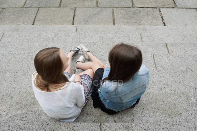 Visão traseira de meninas adolescentes sentadas em passos — Fotografia de Stock