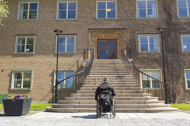 Visão traseira do homem na cadeira de rodas na frente de escadas altas — Fotografia de Stock
