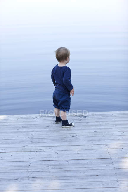 Boy standing on jetty, differential focus — Stock Photo