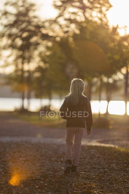 Rear view of girl walking in riverside park — Foto stock