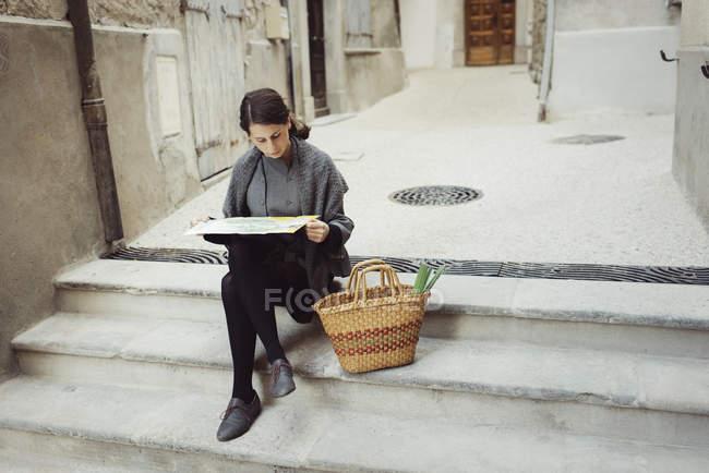 Giovane turista seduto sui gradini e guardando la mappa — Foto stock