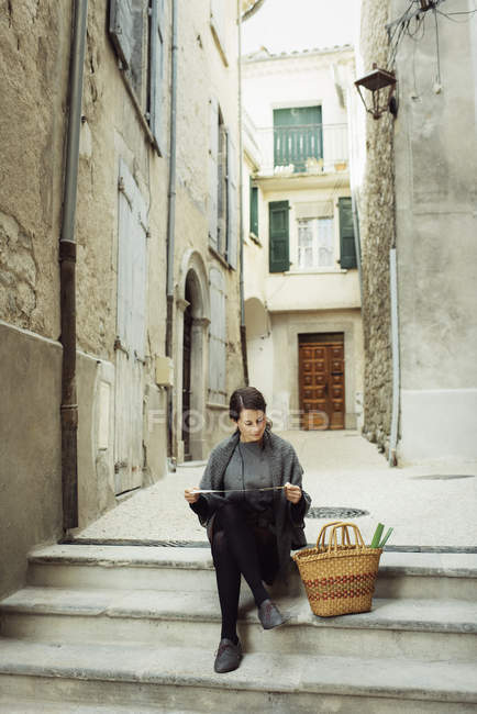 Young tourist sitting on steps and looking at map — Foto stock