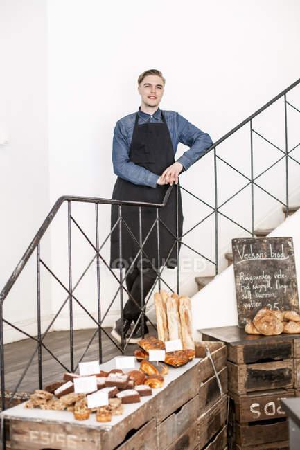 Молодий Бейкер, стоячи на сходах з пекарні в передній — стокове фото