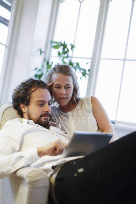 Casal adulto médio usando tablet digital, foco diferencial — Fotografia de Stock