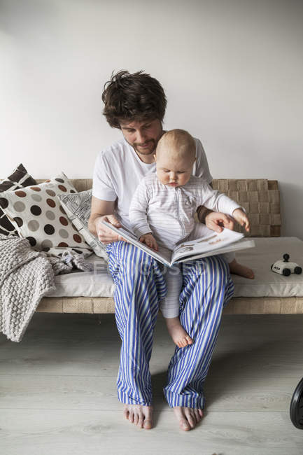 Father reading to baby son at living room — Stock Photo