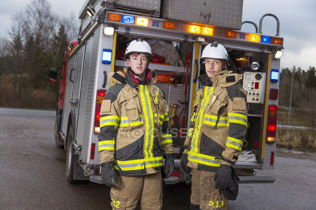 Firefighters in front of fire engine — Stock Photo