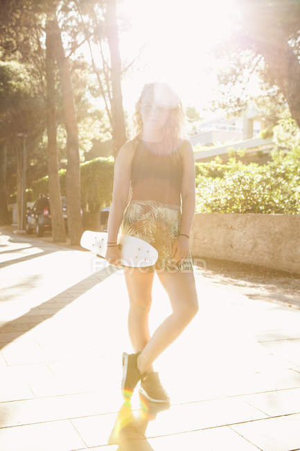 Teenage girl with skate board, lens flare — Stock Photo