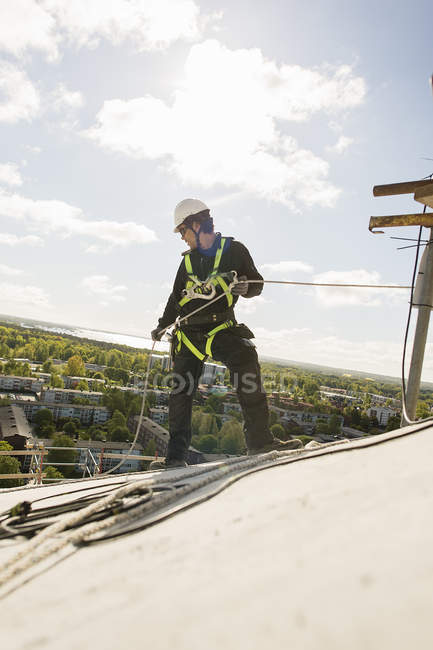 Construction worker in protective workwear rappelling from roof — Stock Photo