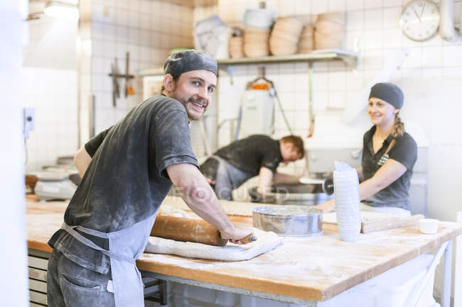 Three bakers making bread in kitchen — Stock Photo